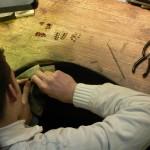 jeune artisan à l'établi en train de fabriquer des bijoux selon la technique du Grenat de Perpignan