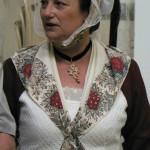 Arlesienne en habillement XVIIIe reconstitué, gardant l'exposition.