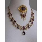 Collier draperie et broche ovale, or jaune à pampilles, sertis de grenats ovales ou poires et demi perles, travail français vers 1850.
