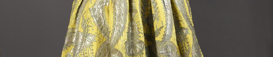 robe volante, vers 1730, lampas fond gros de Tours jaune citron broché soie verte, filé et frisé métalliques argent étincelant à décor stylisé de grenades, corbeille de fleurs et d'un kiosque d'inspiration chinoise inscrits entre les courbes et contre-courbes de feuilles dentelées recourbées.