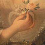 Détail de la main tenant la rose.