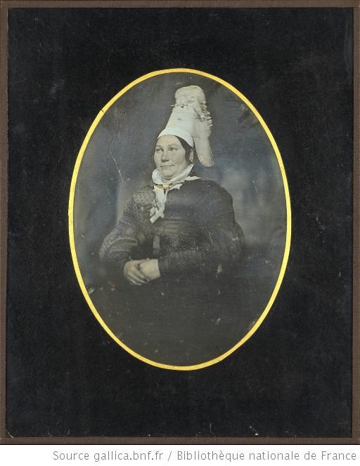 Portrait de femme, à mi-genoux, assise, de trois-quarts à gauche, les mains croisées, portant une coiffe normande, Gallica.bnf.fr
