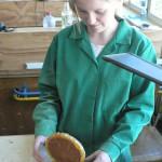 Jeune restauratrice en formation et horloge en ambre des collections de l'école de Turnov en dépôt au Musée.