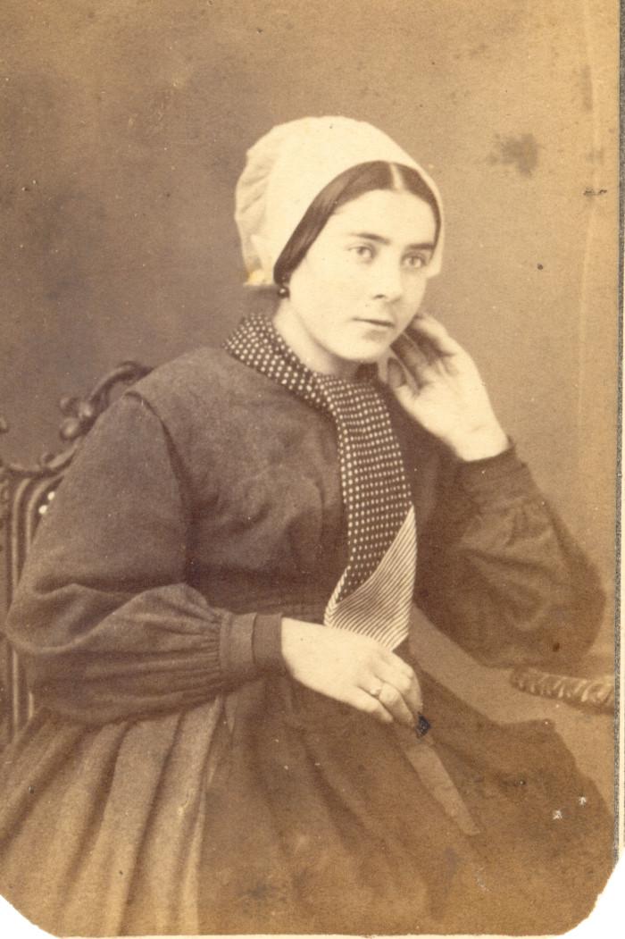 Portrait de jeune femme. C'est une jeune employée de maison portant une robe unie en drap de laine, un tablier et une cravate autour du cou. Sa coiffe est un simple «cofet» de calicot blanc amidonnée. Photographie Bidard frères, Perpignan, ver 1860, collection particulière.