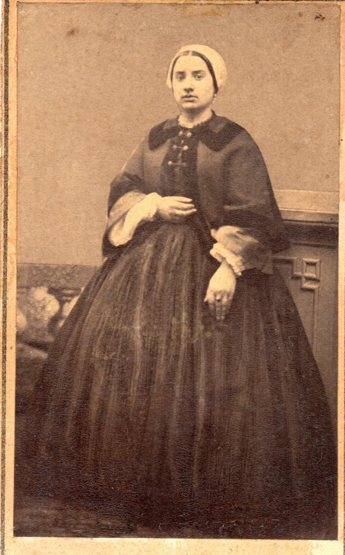 Portrait de jeune femme. Une jeune Catalane portant la coiffe, en robe à crinoline. Elle porte une veste cape qui lui sert de manteau. Photo Bataille, Perpignan, vers1863, collection Institut du Grenat.
