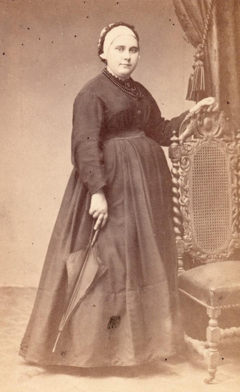 Portrait de Catalane. Dans une tenue simple, cette jeune Catalane, probablement enceinte, a gardé son ombrelle à la main. La coiffe de type «cofet», de simple tissu, est ornementée d'un ruban sombre formant une auréole. Elle porte aussi autour du cou un collier de lourdes perles de jais, signes probables du demi deuil. Photographie Cabibel, Perpignan, vers 1870, collection Institut du Grenat.
