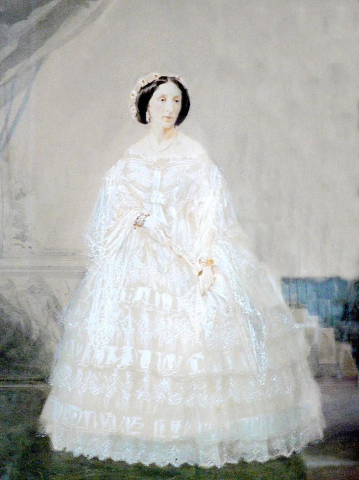 Portrait de la Comtesse Charlotte de LAZERME (1822-1888). Son haut rang lui permet de se montrer avec une vaporeuse crinoline. On perçoit à ses poignets d'imposants bracelets en or et pierreries. Son visage est mis en valeur par les boucles d'oreilles et la coiffe à la mode, ornementée de fleurs. Une simple chaîne est suspendue à son cou. Perpignan trouve en Charlotte de LAZERME l'une de ses égéries de mode. Sa fortune en fait une femme du monde, position propice à devenir un modèle d'élégance et de nouveauté pour les femmes du Roussillon. Aquarelle, vers 1860, Perpignan, collection particulière.
