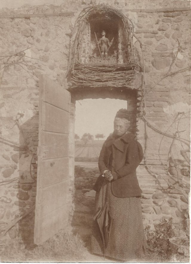 Madame Sebe à la porte du jardin sous la niche dédiée à saint Gauderique.